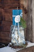 Advent arrangement of blue candle on top of vintage-style preserving jar on snowy wooden board