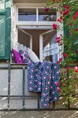 Crocheted Granny-style blanket and cushions on windowsill of traditional lattice window