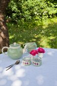 Tealight holders with crocheted covers and vintage coffee service on garden in dappled shade
