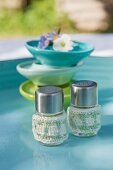 Salt and pepper shakers with hand-crocheted covers on turquoise garden table