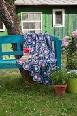 Crocheted blanket with hexagonal pattern in shades of blue and purple on garden bench in front of cabin