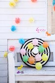 Colourful balloons pinned to dartboard below garlands of paper flowers on white wooden wall