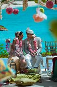 Indian bride and groom adorned with pink flower garlands against backdrop of turquoise sea