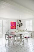 White table and wooden chairs below chandelier in rustic interior with white wooden floor and modern artwork on wall