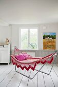 Comfortable hammock on metal frame on white wooden floor in rustic interior
