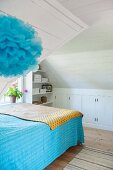 Bed with blue bedspread in white wood-clad attic room with blue pompom in foreground