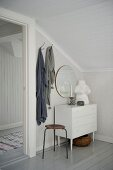 Vintage stool and white chest of drawers in corner below sloping ceiling