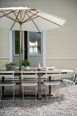 Seating area below parasol on gravel terrace outside wooden house