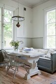 White vintage table between pale grey chairs and bench below window