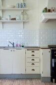 Vintage kitchen counter with base units below white-tiled splashback