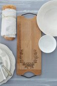 Ornate wooden bread board on table
