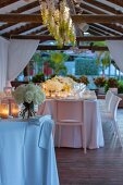 Wedding dinner table festively decorated with candle lanterns and bouquets on roofed terrace