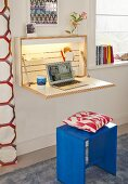 A simple, wall-mounted cupboard with a fold-down desk, indirect lighting and a laptop