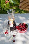 Karaffe mit gebasteltem Etikett, Gläser und eine Schale mit Kirschen