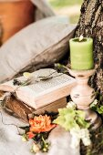 Romantic seating area with candle and flowers next to open book on tree trunk
