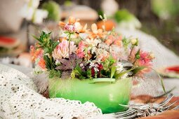 Flower arrangement in green saucepan outdoors