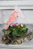 Bird ornaments hand-crafted from coloured paper and corrugated cardboard decorating potted primula wrapped as gift