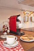 Kaffeetasse auf kariertem Geschirrtuch und gefüllte Waffeln, im Hintergrund Kaffeemaschine und Aufbewahrungsglas mit Kaffeekapseln