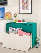 Klappbarer grüner Tisch mit untergeschobener weißer Sitzbank und Schublade; Stauraumlösungen mit platzsparendem Mobiliar