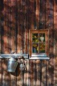 Hakenleiste an Holzhausfassade mit Licht- und Schattenspiel, daneben kleines Sprossenfenster