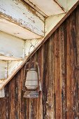 Alte Gaslaterne an Nagel unter einem Treppenlauf, dahinter Holzfassade