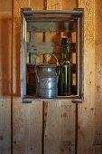 Alte Milchkanne und Flasche mit Bügelverschluss als Deko in Obstkiste an der Wand eines Holzhauses