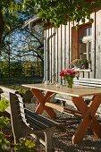 Rustikaler Sitzplatz in der Herbstsonne vor Holzhaus