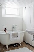 Free-standing bathtub and wood-clad wall in vintage-style bathroom
