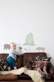 Kleinkind auf braunem Lederrsofa mit Schaffell vor Wandtattoos mit Tiermotiven