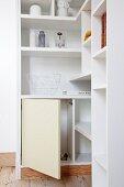 White, custom-made corner shelves with open cupboard door