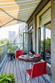Yellow awning, wooden table and red chairs on urban balcony