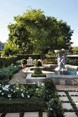 Landscaped garden with fountain, stone sculpture, clipped hedged and paved paths