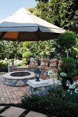 Circular hearth with stone wall and comfortable seat cushions on bench below parasol