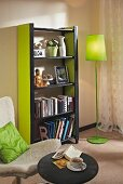 Black and green DIY shelving made from wooden slats and MDF panels in loving room