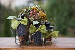 Nuts and pine cones in three storage jars with black lids and labels in front of posy of dried flowers