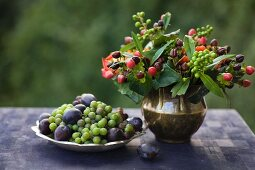 Autumn posy of St John's wort berries in brass vase next to zinc dish of grapes and plums
