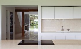 View across counter to modern white fitted kitchen and open doorway