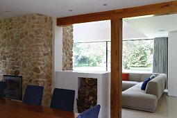 View across dining table and half-height firewood store into lounge area