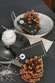 Decorative china bowls, silver owl and pine cones