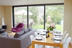Set dining table, white classic shell chairs, lounge area and glass wall with garden view
