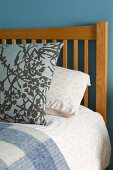 Patterned pillow on bed with wooden headboard