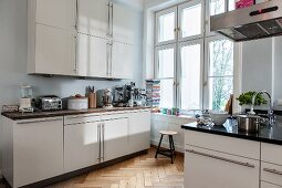 Fitted kitchen with white doors and herringbone parquet floor in period apartment