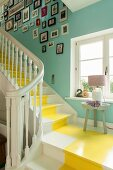 White-painted wooden staircase with yellow central stripe in stairwell with turquoise-painted walls and gallery of pictures