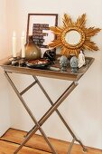 Lit candles, ornaments and mirror with gilt starburst frame on metal tray table