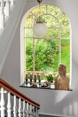Bust of woman and candlesticks on sill of arched window with garden view in stairwell