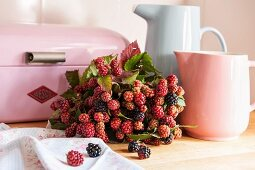 Bouquet of blackberries amongst jugs and bread bin in pastel shades