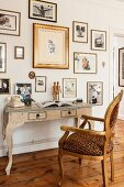 Baroque chair with leopard-pattern upholstery at antique console table below gallery of pictures on wall