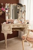 Jewellery, perfume bottles and cosmetics on dressing table in ornate Rococo style