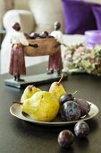 Dish of pears and plums in front of ethnic figurine