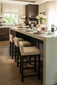 Elegant breakfast bar and upholstered bar stools in open-plan kitchen